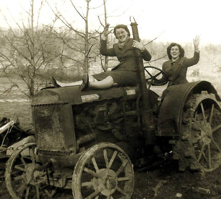 two women riding a tractor
